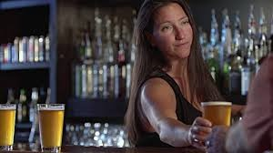 woman bartender serving glass of beer