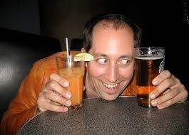 man with 2 drinks in his hand at bar