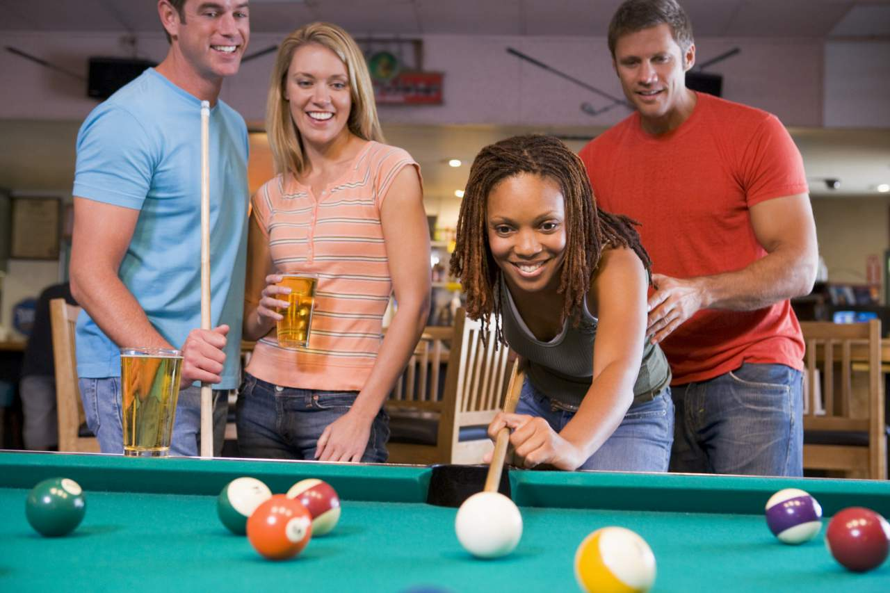 playing billiards with a pint of beer